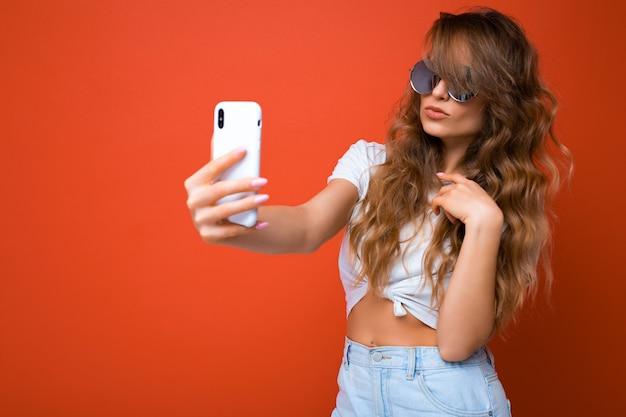 Nahaufnahmefoto der erstaunlichen schönen jungen blonden frau, die handy hält, das selfie foto unter verwendung macht