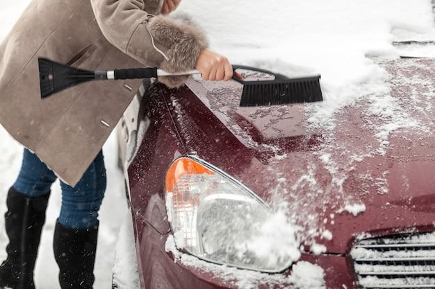 Nahaufnahmefoto der frau, die bürste hält und schnee vom auto säubert