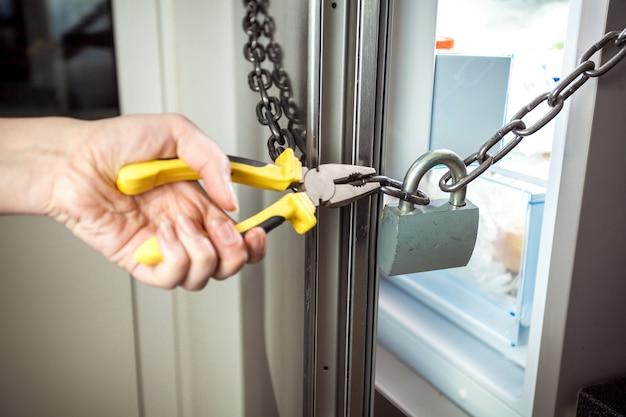 Nahaufnahmefoto der frau, die kette am kühlschrank mit zange durchschneidet