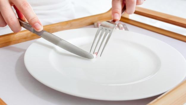 Nahaufnahmefoto der frau, die medizinpille mit messer und gabel isst. konzept der diät, gewichtsverlust und medizin.