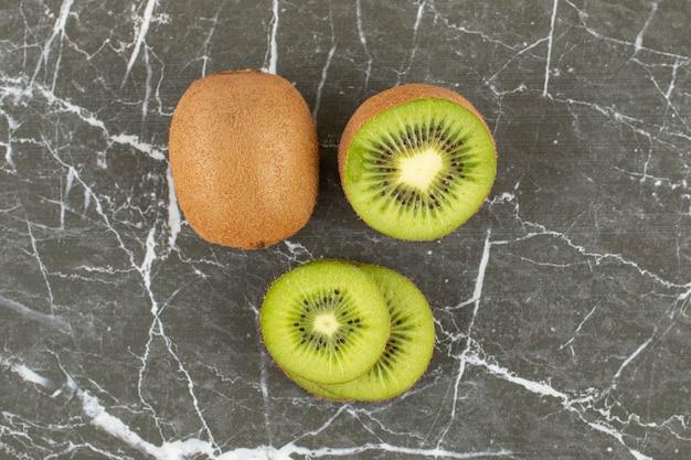 Nahaufnahmefoto der ganzen und geschnittenen kiwi auf schwarz.