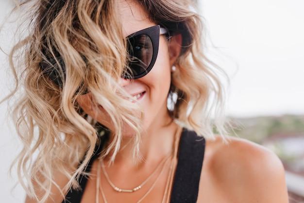 Nahaufnahmefoto der gebräunten frau mit trendigem haarschnitt. porträt des lachenden weiblichen modells, das in der sonnenbrille aufwirft.
