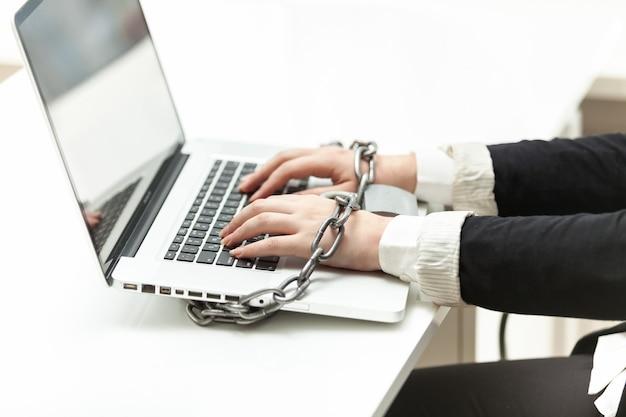 Nahaufnahmefoto der geschäftsfrau, die durch eine kette an den laptop gesperrt ist
