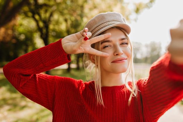 Nahaufnahmefoto der glänzenden schönen blondine im trendigen roten pullover und im hellen hut, die glückliches selfie im herbst machen.