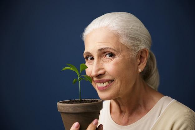 Nahaufnahmefoto der glücklichen gealterten frau, die junge pflanze an der stelle zeigt