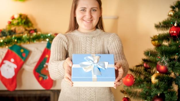 Nahaufnahmefoto der glücklichen lächelnden jungen frau, die weihnachtsgeschenk in der schönen schachtel mit seidenbandbogen gibt