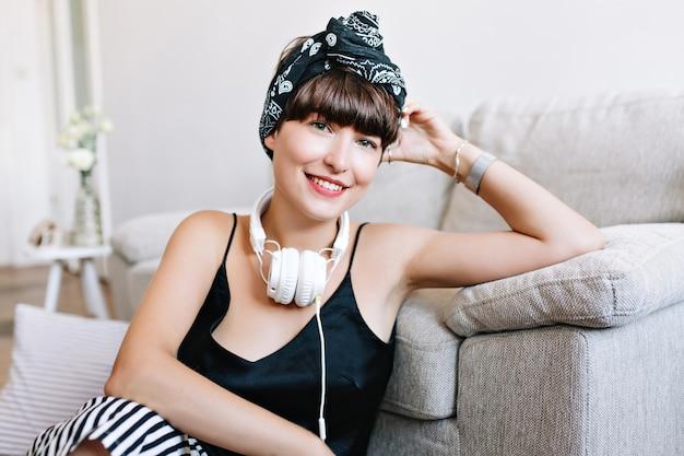 Nahaufnahmefoto der glückseligen jungen dame, die schwarzes seidentank-top trägt, das zu hause am wochenende entspannt