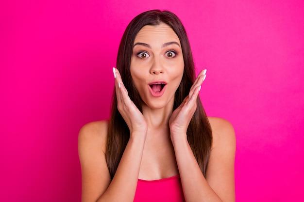 Nahaufnahmefoto der hübschen dame mit erstaunlichem langem haar, das mit offenem mund auf verkaufspreisen schaut, tragen helle off-shoulder-spitze lokalisierten lebendigen rosa farbhintergrund