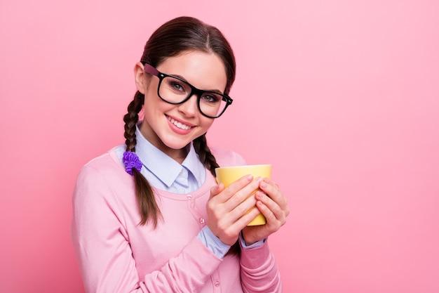 Nahaufnahmefoto der hübschen studentendame, die hände heiße frische getränketasse hält kleine pause hausaufgaben überglücklich gute laune tragen hemd pullover spezifikationen isoliert pastellrosa farbhintergrund