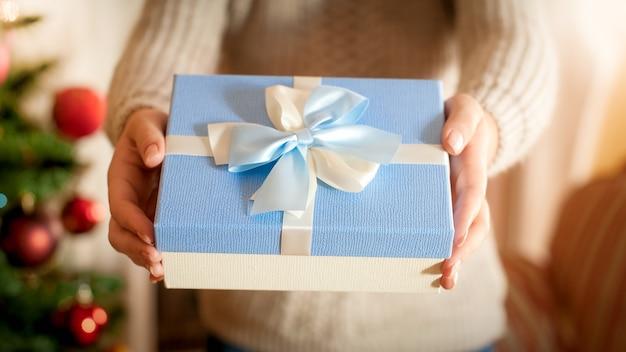 Nahaufnahmefoto der jungen frau, die am weihnachtsbaum steht und blaue geschenkbox mit seidenbandbogen gibt. perfektes bild für winterferien und feiern