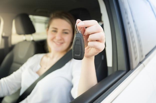 Nahaufnahmefoto der jungen frau, die auto fährt und autoschlüssel zeigt
