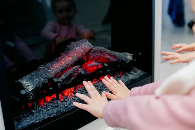 Nahaufnahmefoto der kinderhände, die durch einen kamin wärmen. fühlen sie sich am lagerfeuer zu hause wohl.