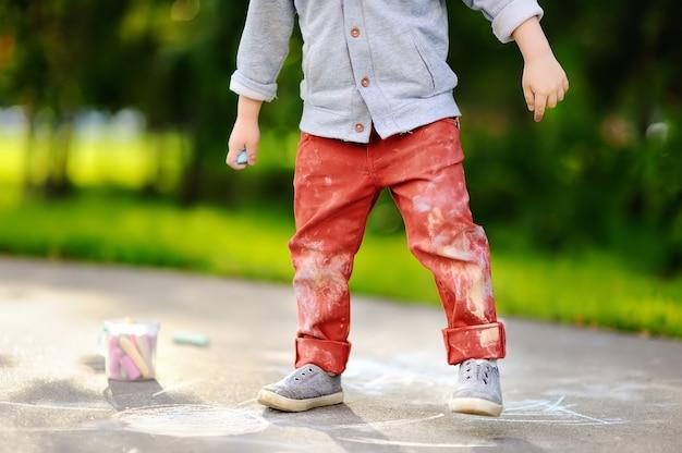 Nahaufnahmefoto der kleinkindjungenzeichnung mit farbiger kreide auf asphalt.