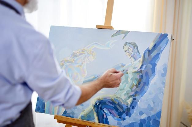 Nahaufnahmefoto der leinwand auf staffelei gemalt mit pinsel durch professionellen künstler, blaue malerei, meisterwerk
