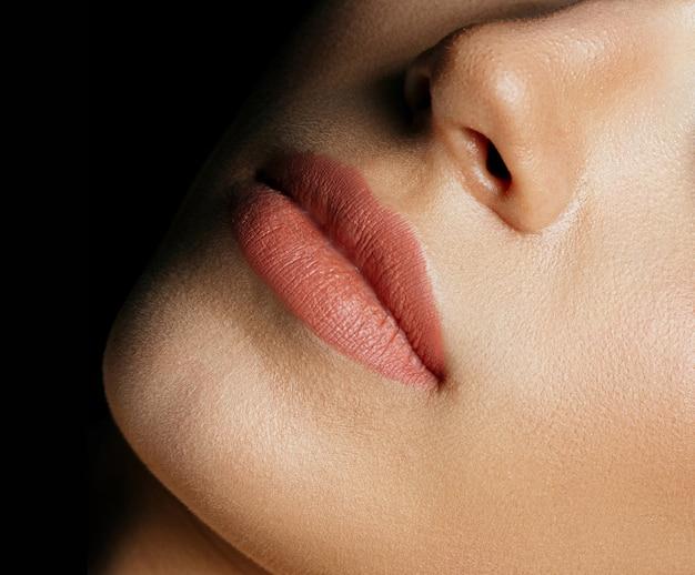 Nahaufnahmefoto der lippen der perfekten frau nach dem permanenten make-up-verfahren. platz für text