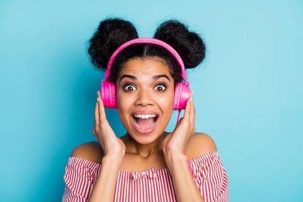 Nahaufnahmefoto der lustigen schönen dunklen hautdame hören musik moderne technologie kopfhörer offener mund lieblingslied tragen trendiges rotes weiß gestreiftes hemd von den schultern isoliert blaue farbwand