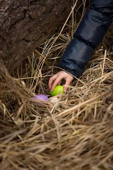 Nahaufnahmefoto der mädchenhand, die osterei aus dem nest nimmt