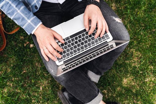 Nahaufnahmefoto der männlichen hände mit einem männlichen freiberufler des laptops, der über computerblogger, der neuen artikel schreibt, mit dem internet verbindet