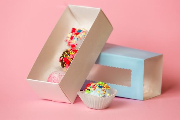 Nahaufnahmefoto der offenen geschenkbox mit bunten kuchenbällchen und bonbons mit streuseln über rosafarbener oberfläche
