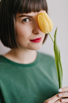 Nahaufnahmefoto der reizenden europäischen frau mit dem braunen haar, das mit blume aufwirft. innenporträt des erfreuten stilvollen mädchens mit gelber tulpe.