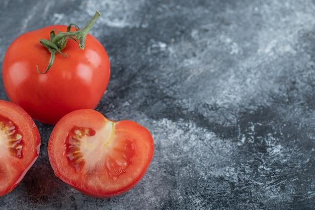 Nahaufnahmefoto der roten frischen tomaten ganz oder geschnitten. hochwertiges foto