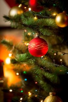 Nahaufnahmefoto der roten weihnachtskugel auf dem tannenbaum neben dem kamin