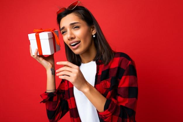 Nahaufnahmefoto der schönen emotionalen jungen brunettefrau, die auf rotem hintergrundwand trägt, lokalisiert wird