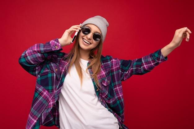 Nahaufnahmefoto der schönen glücklichen positiven jungen blonden frau, die purpurrotes hemd des hipsters und lässig trägt