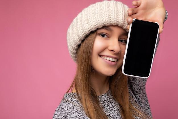 Nahaufnahmefoto der schönen lächelnden entzückenden jungen blonden frau, die beiläufigen grauen pullover trägt und