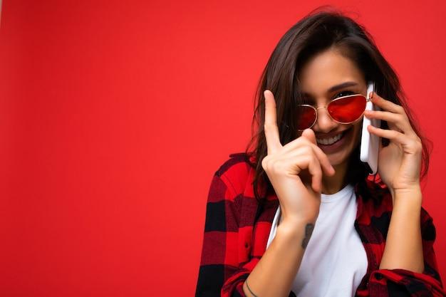 Nahaufnahmefoto der sexy hübschen glücklichen jungen brunetfrau, die stilvolles rotes hemd weißes t-shirt und rote sonnenbrille trägt lokalisiert über rotem hintergrund, der auf dem handy kommuniziert, das kamera betrachtet.