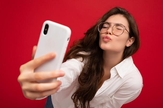 Nahaufnahmefoto der sexy schönen positiven jungen brünetten frau, die weißes hemd und optisches trägt