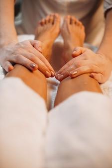Nahaufnahmefoto der spa-massagesitzung, die von einem vorsichtigen arbeiter im salon auf den beinen des kunden gemacht wird