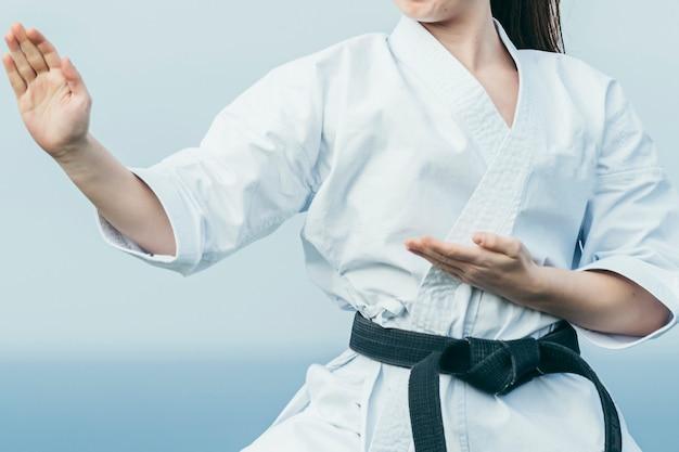 Nahaufnahmefoto der unbekannten karate-sportlerin, die sich auf den angriff vorbereitet