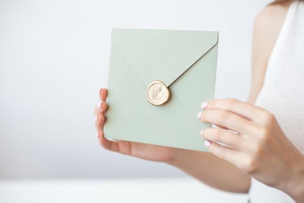 Nahaufnahmefoto der weiblichen hände, die einladungsumschlag mit einem goldwachssiegel, geschenkgutschein, postkarte, hochzeitseinladungskarte halten