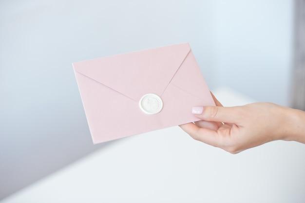 Nahaufnahmefoto der weiblichen hände, die einladungsumschlag mit einem wachssiegel, geschenkgutschein, postkarte, hochzeitseinladungskarte halten.