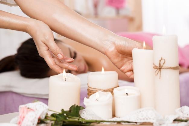 Nahaufnahmefoto der weiblichen hände, die kerzen am spa-salon nehmen