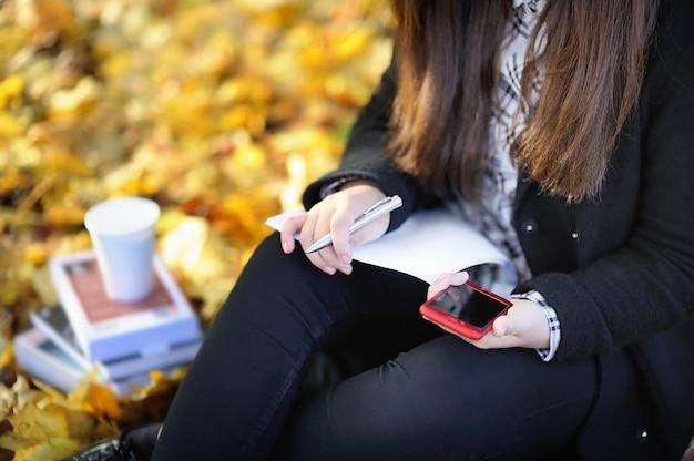 Nahaufnahmefoto des asiatischen studentenmädchens, das ihren handy während des studierens / des arbeitens verwendet