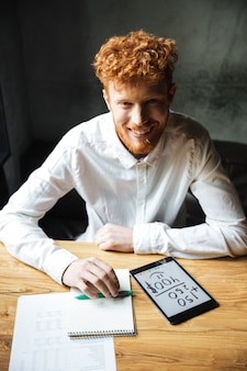 Nahaufnahmefoto des bärtigen mannes des jungen lächelnden lesekopfes im weißen hemd unter verwendung der digitalen tablette am arbeitsplatz, schauend