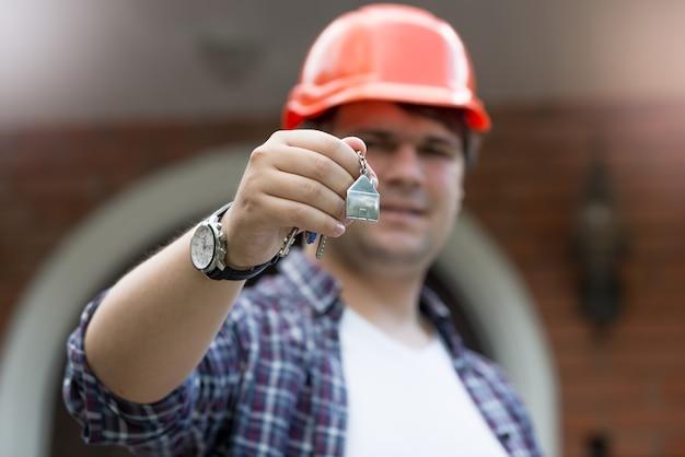 Nahaufnahmefoto des bauarbeiters, der schlüssel vom neuen haus in der hand hält