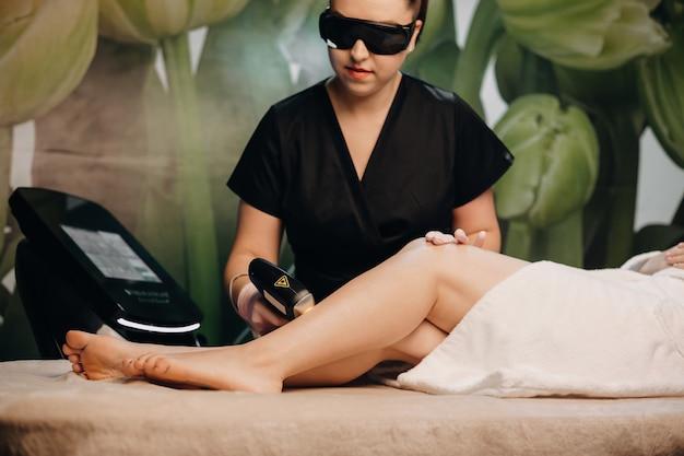 Nahaufnahmefoto des epilierungsverfahrens mit modernen apparaten im salon