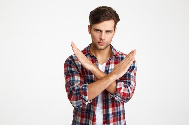 Nahaufnahmefoto des ernsten gutaussehenden jungen mannes, der stoppgeste mit gekreuzten händen zeigt
