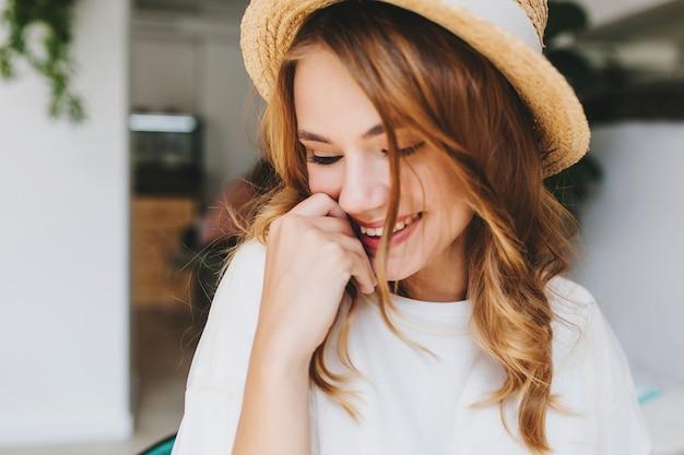 Nahaufnahmefoto des erstaunlichen glücklichen mädchens mit dem blassen hautschüchternen lachen und bedecken gesicht mit hand