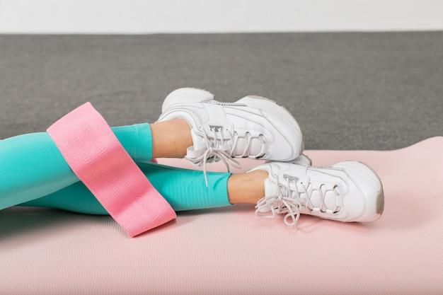 Nahaufnahmefoto des expander-gummibands auf frauenbeinen.