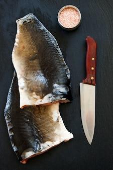 Nahaufnahmefoto des frischen rohen fischfilets mit seesalz und messer auf schwarzem konkretem tabellenhintergrund