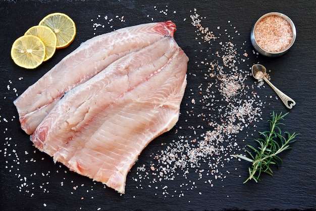 Nahaufnahmefoto des frischen rohen fischfilets mit seesalz und zitrone auf schwarzem konkretem tabellenhintergrund.