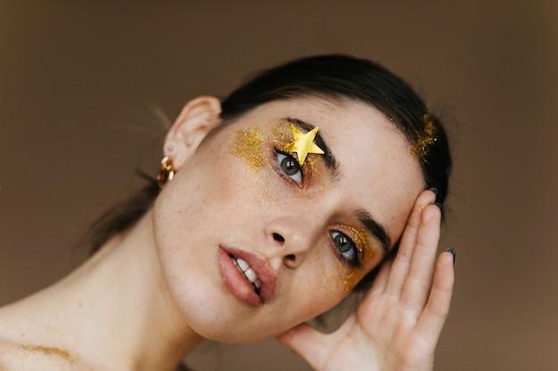 Nahaufnahmefoto des glückseligen blassen mädchens. neugierige junge frau mit party make-up.