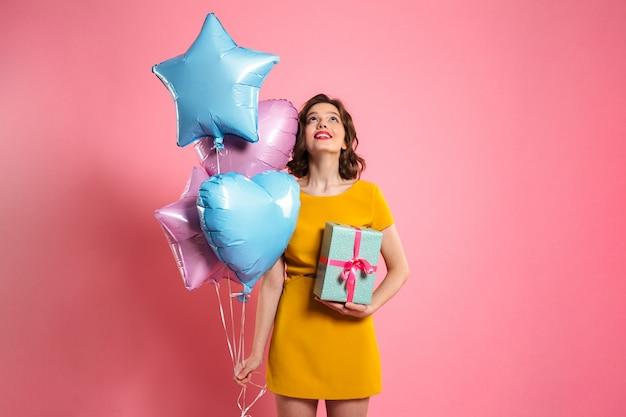 Nahaufnahmefoto des hübschen geburtstagskindes, das geschenk und luftballons hält und nach oben schaut