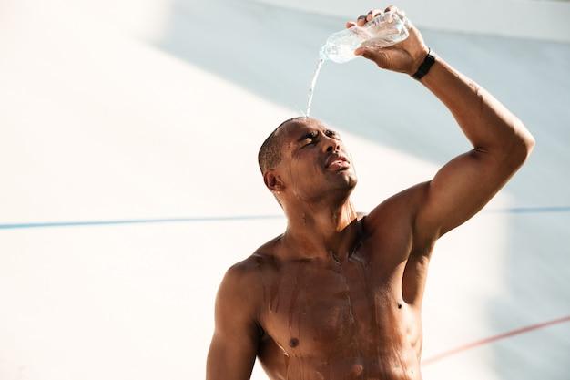 Nahaufnahmefoto des jungen afrikanischen sportmannes, der wasser auf seinem kopf ausschüttet und nach dem training ruht