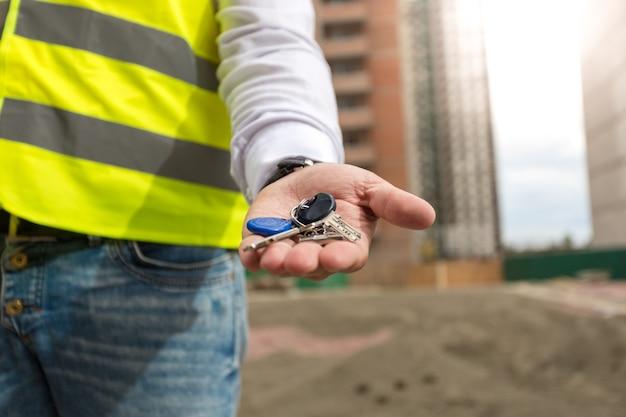 Nahaufnahmefoto des jungen architekten, der schlüssel aus dem neuen zuhause zur hand hält