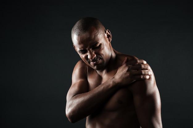 Nahaufnahmefoto des jungen hemdlosen afroamerikanischen mannes mit schulterschmerzen